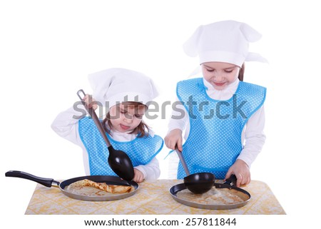 Little children cooking pancakes. Two cute girls playing as chefs. Surprise for Mothers Day. Isolated on a white background. - stock photo