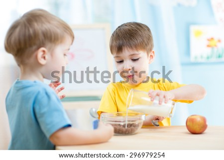 little children eating healthy food at home - stock photo
