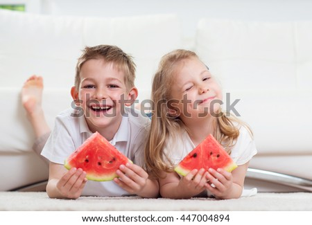 Little children eating watermelon at home - stock photo