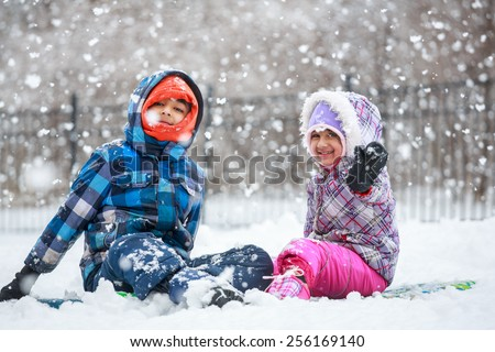 Little Children Enjoying Snowfall and Playing in the Snow - stock photo