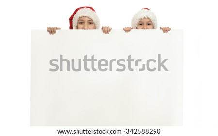 Little children in christmas hats holding white poster - stock photo