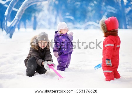 Little children in winter clothes having fun in park at the snowy winter day. Children play outdoors. Outdoor active for family vacation