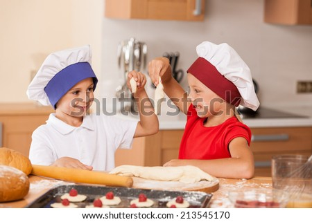 little children making bakery and smiling. brother and sister having fun at kitchen table  - stock photo