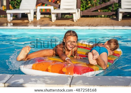 Little children on inflatable mattress in swim pool. Smiling kids playing and having fun in swimming pool with air mattress. Boy and girl playing in water. Summer vacations concept.