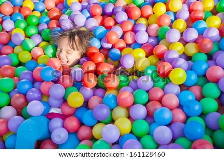 little children on the background of many multicolored small balls