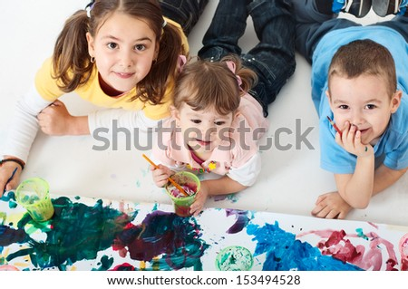 Little children painting, lying on the floor