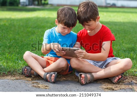 Little children playing on tablet at outdoor - stock photo