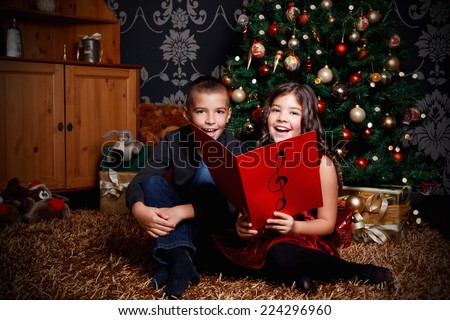 Little children singing a song at Christmas Eve - stock photo