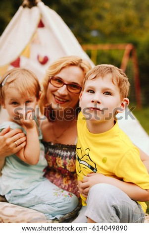 Little children sit on mother's knees on picnic