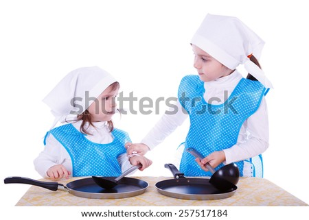 Little children with pans. Two cute girls playing as chefs. Surprise for Mothers Day. Isolated on a white background. - stock photo