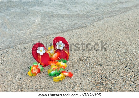 Little childs red flipflops with white flowers are lodged in the sand along with a flower lei.  Both are laying on a salt and pepper beach on the Kohala Coast of the Big Island of Hawaii. - stock photo