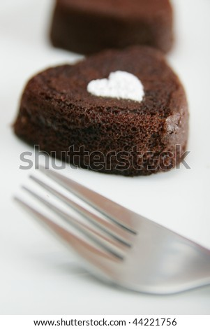 Little chocolate cake with heart powder sugar - stock photo