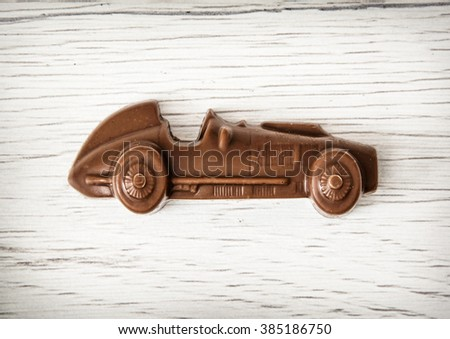 Little chocolate car figure on wooden background. Sweet art and food. - stock photo