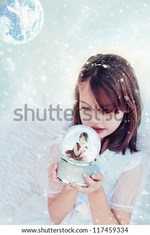 Little Christmas angel holds a snow globe and watches a little girl inside blowing snow.