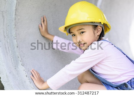 Little civil engineer girl inspecting  huge concrete pipe and playing