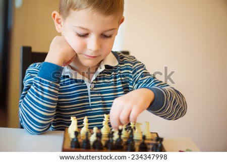 Little clever boy concentrated and thinking with chess - stock photo