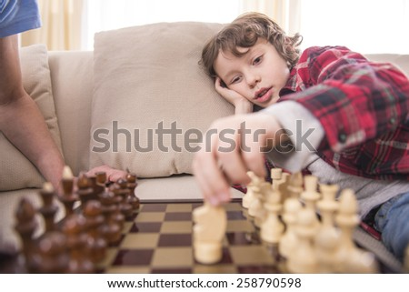 Little clever boy concentrated and thinking with chess. - stock photo