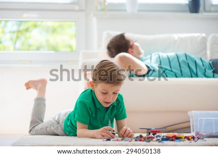Little clever boy play with blocks, father is at background - stock photo