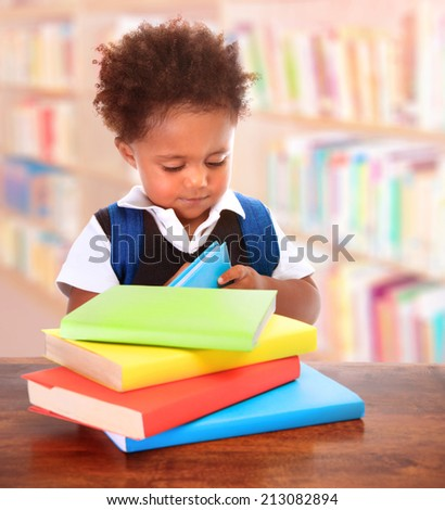 Little clever preschooler in the library, reading books, cute African American boy preparing to go to first grade, enjoying study, back to school