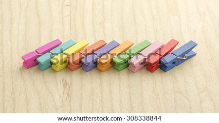 Little colorful paperclips placed on the wood background. - stock photo