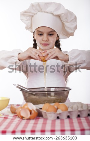 Little cook girl in a white apron breaks eggs in a deep dish, isolated on white background - stock photo