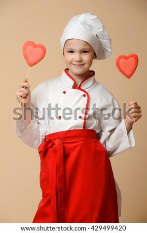 Little cook girl tasting cookies - stock photo