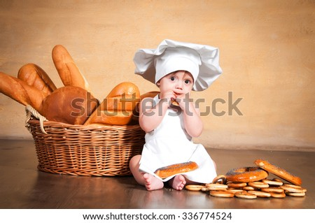 Little cook in a chef's hat eats bagels near wicker baskets of pastries and bakery products - stock photo