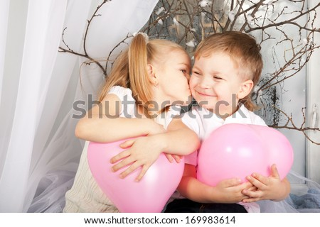 Little couple of kids hugging, kissing and holding heart balloons. Valentine's Day and love concept.  - stock photo