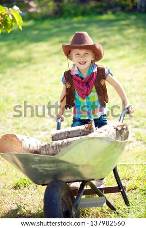 Little cowgirl pushing fire woods in wheelbarrow