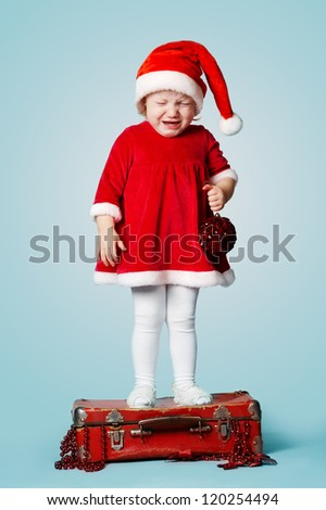little crying girl standing on red suitcase with gifts
