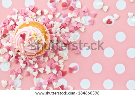Little cupcake with pink frosting and sprinkles - stock photo