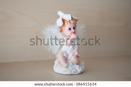 Little Cupid on wood background - stock photo