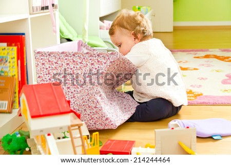 Little curious baby in children�´s room