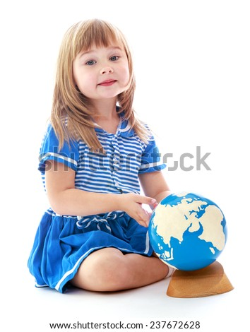 Little curious girl examines the globe sitting on the floor isolated on white background.Happy childhood, adolescence, the development of the family concept. - stock photo