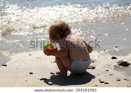 Little curious smart blonde baby boy in sitting on sand sunny day outdoor playing with plastic toys on natural wavy ocean water beach background, horizontal picture