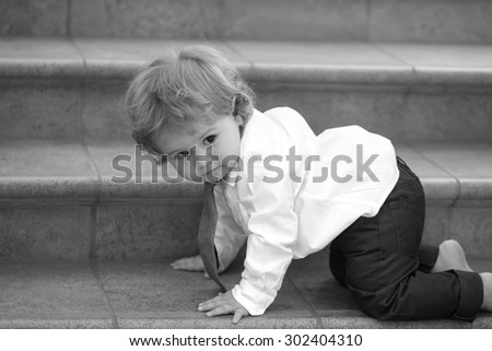 Little curious stylish baby boy with curly hair in formal shirt necktie and trausers creeping barefoot on stone stairs looking away black and white, horizontal picture - stock photo