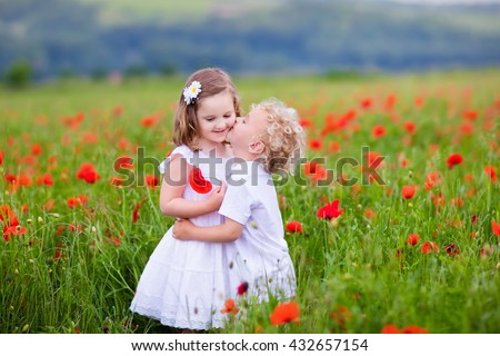Little curly blond boy and girl play in poppy flower field. Child picking red poppies. Toddler kid in summer meadow. Family vacation in the country. Children pick flowers, hug and kiss. Siblings love. - stock photo