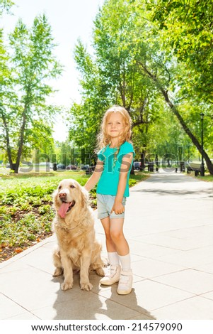 Little curly blond girl with dog in sunny park - stock photo