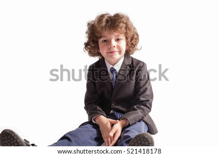 Little curly boy in a business suit sitting on the floor and looking into the camera. White background.