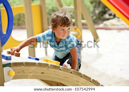 Little curly boy is playing on playground. - stock photo