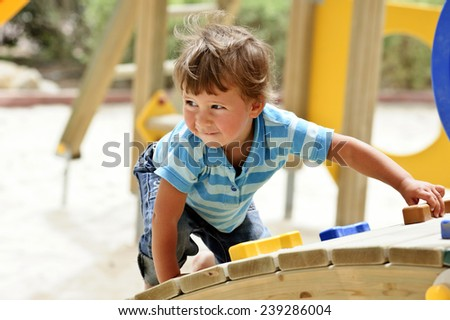 Little curly boy is playing on playground - stock photo