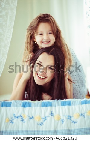 Little curly girl lies on mother's back and smiles
