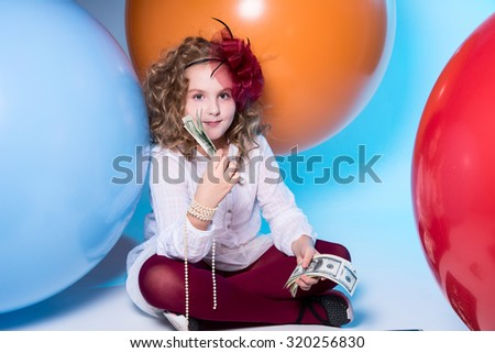 Little curly girl school girl with dollars in hand on the background of large rubber balls.
