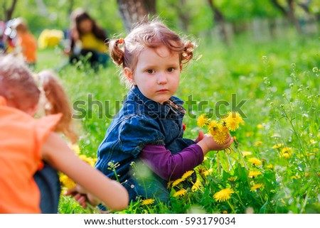 Little curly girl sitting on the grass. A child holding a dandelion. Girl with two tails on head smiling.