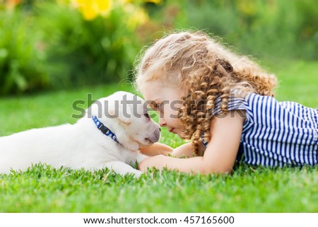 Little curly girl with a labrador puppy, outdoor summer