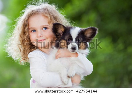 Little curly girl with a papillon puppy, outdoor summer - stock photo
