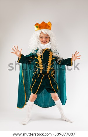Little curly king stands legs apart and hands. Grey background.