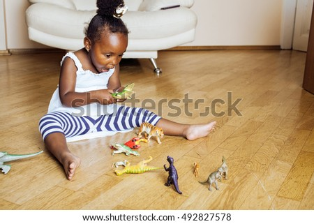 little cute african american girl playing with animal toys at home, pretty adorable princess in interior happy smiling, lifestyle people concept
