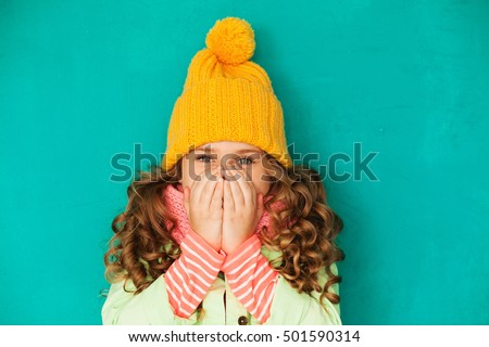 Little cute amazed girl wearing warm cap and scarf feeling cold
