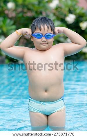 Little cute Asian girl on bikini suit in swimming pool. - stock photo